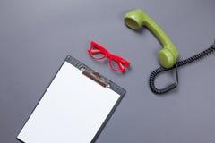 Bordo di affari e microtelefono verde con i vetri fotografia stock