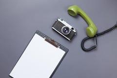 Bordo di affari e microtelefono verde con la retro macchina fotografica fotografie stock libere da diritti