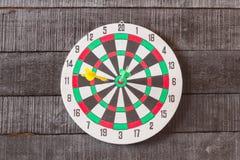 Bordo di dardo con la freccia dei dardi nel centro dell'obiettivo sul backgro di legno Fotografie Stock