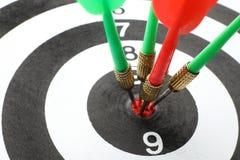 Bordo di dardo con le frecce di colore che colpiscono obiettivo fotografie stock