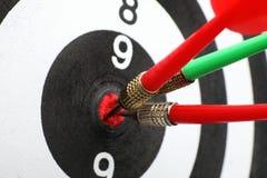 Bordo di dardo con le frecce di colore che colpiscono obiettivo immagini stock libere da diritti