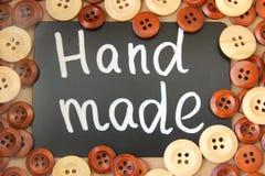 Bordo di gesso con il ` fatto a mano del ` dell'iscrizione circondato dai bottoni di legno marroni e bianchi Immagine Stock