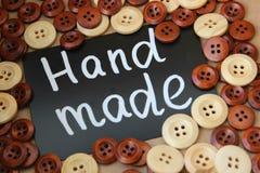 Bordo di gesso con il ` fatto a mano del ` dell'iscrizione circondato dai bottoni di legno marroni e bianchi Fotografie Stock