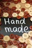 Bordo di gesso con il ` fatto a mano del ` dell'iscrizione circondato dai bottoni di legno marroni e bianchi Fotografia Stock