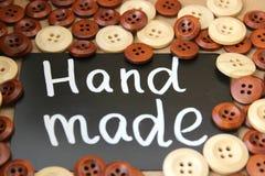 Bordo di gesso con il ` fatto a mano del ` dell'iscrizione circondato dai bottoni di legno marroni e bianchi Immagini Stock