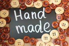 Bordo di gesso con il ` fatto a mano del ` dell'iscrizione circondato dai bottoni di legno marroni e bianchi Fotografia Stock Libera da Diritti
