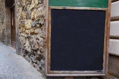 Bordo di gesso nero della via sulla vecchia parete del caffè fotografie stock