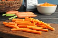 Bordo di legno con i bastoni di carota immagini stock libere da diritti