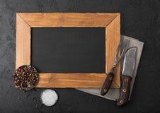 Bordo di legno del menu e coltello d'annata e forcella della carne sull'asciugamano di cucina e sul fondo di pietra nero della ta immagini stock libere da diritti