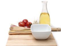 Bordo di legno, olio d'oliva con i pomodori ciliegia sulla cucina Fotografia Stock