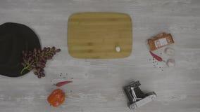 Bordo di legno quadrato sulla tavola Sulla tavola sia: cappello, peperoni, vassoio, macchina fotografica e prosciutto La mano fem stock footage