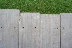 Bordo di legno sul fondo dell'erba verde fotografia stock