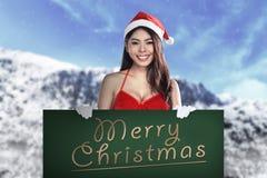 Bordo di Santa Woman Holding Merry Christmas Fotografie Stock Libere da Diritti