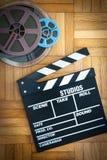Bordo di valvola di film e bobina di film sul pavimento di legno Immagini Stock Libere da Diritti