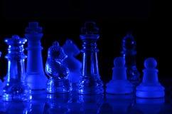 Bordo di vetro blu del gioco di scacchi su fondo scuro fotografia stock libera da diritti