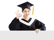 Bordo laureato dello spazio in bianco di rappresentazione della femmina felice con il gesto giusto Fotografie Stock
