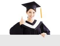 Bordo laureato dello spazio in bianco di rappresentazione della femmina felice con il pollice su Fotografia Stock Libera da Diritti