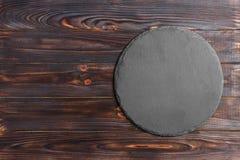 Bordo naturale rotondo dell'ardesia Supporto grigio scuro dell'ardesia su fondo di legno Utensile naturale del ristorante immagine stock