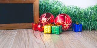Bordo nero con i contenitori di regalo e palle con fondo su di legno Fotografia Stock