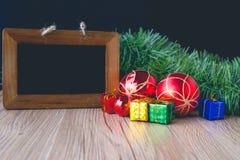 Bordo nero con i contenitori di regalo e palle con fondo su di legno Fotografia Stock Libera da Diritti