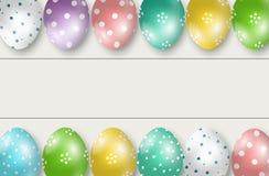 Bordo variopinto delle uova di Pasqua il doppio rasenta il fondo di legno bianco Fotografia Stock