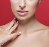 Bordos bonitos e ombros do nariz da mulher que tocam em seu pescoço pelos dedos perto acima do retrato do estúdio no vermelho Imagem de Stock Royalty Free