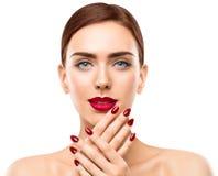 Bordos da cara da beleza da mulher e pregos, verniz para as unhas vermelho do batom fotografia de stock royalty free