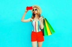 Bordos de sopro da mulher feliz que tomam a imagem do selfie pelo telefone com os sacos de compras no t-shirt colorido, chapéu d fotos de stock royalty free