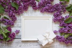 Bordr of purple lilac flowers and white frame for text and invitation. View from above. Bordr of purple lilac flowers and white frame for text and invitation royalty free stock images