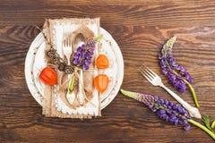Bordsservis med den violett Lupines, physalisen och bestick Royaltyfri Fotografi
