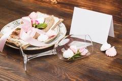 Bordsservis med ljus - rosa rosor och marängar Arkivbilder