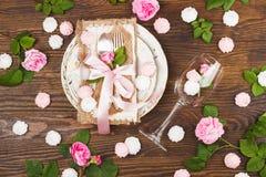 Bordsservis med ljus - rosa rosor och marängar Arkivfoto