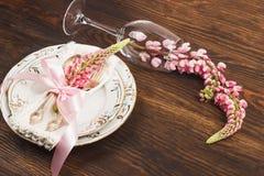Bordsservis med rosa lupines och bestick Arkivfoto