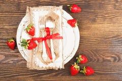 Bordsservis och bestick med jordgubben Arkivbild