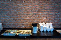 Bordsservis och lerkärl med bakgrund för tegelstenvägg i restaurang arkivbild