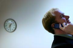 Borduhr u. junger Mann auf Mobiltelefon stockfotos