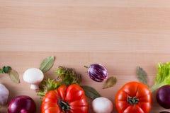 Bordure de différents légumes aiment la tomate, les aubergines, les oignons, la salade et les épices sur le fond en bois photo libre de droits
