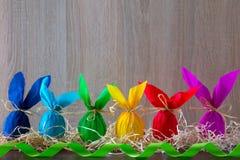 Bordure de los huevos de Pascua bajo la forma de conejo en fondo marrón claro con la cinta verde Adornamiento del día de fiesta Imagenes de archivo