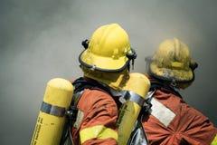 Bordure de lutte contre l'incendie de deux sapeurs-pompiers avec de la fumée foncée Photos libres de droits