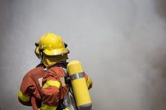 Bordure de lutte contre l'incendie de deux sapeurs-pompiers avec de la fumée foncée Photographie stock