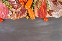 Bordure of different Spanish appetizer, like fuet, jamon, chorizo, bacon and lomo embuchado wiht spice on black wooden. Bordure of different Spanish appetizer Stock Image