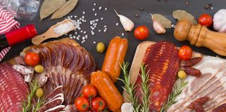 Bordure of different spanish embutidos, like fuet, jamon, chorizo, bacon and lomo embuchado with red wine, olives and spice. Bordure of different spanish Royalty Free Stock Photography