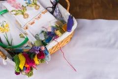 Borduurwerk en allen noodzakelijk voor deze hobby Het borduurwerkhoepel van de draadschaar in een rieten mand stock foto's
