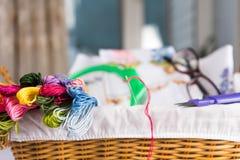 Borduurwerk en allen noodzakelijk voor deze hobby Het borduurwerkhoepel van de draadschaar in een rieten mand stock afbeeldingen