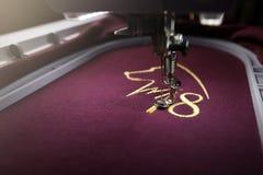 Borduurwerk met borduurwerkmachine van hondsilhouet en nummer 2018 in goud op Bordeauxstof royalty-vrije stock foto
