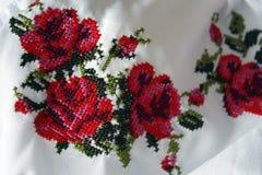 Borduurwerk met mooie kleurrijke rode rozen en groene bladeren, close-up Dwars-steektextuur, volkskostuum stock afbeeldingen