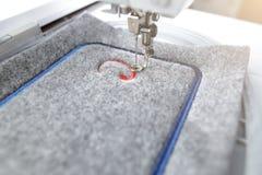 borduurwerk van het rode die van letters voorzien op grijs door een moderne borduurwerkmachine wordt gevoeld in helder zonnig lic stock afbeelding