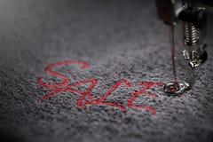 borduurwerk van rode het van letters voorzien VERKOOP op zachte grijze stof met borduurwerkmachine - sluit omhoog stock afbeelding