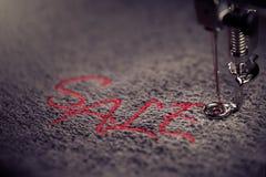 borduurwerk van rode het van letters voorzien VERKOOP op zachte grijze stof met dicht omhoog gekleurde borduurwerkmachine - - mar stock afbeelding