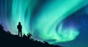 Borealis αυγής και σκιαγραφία μιας γυναίκας με το σακίδιο πλάτης τη νύχτα στοκ φωτογραφία